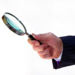 A hand with a magnifying glass